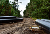Natural Gas Pipeline Construction. Laying oil pipe in a trench in the ground. Petrochemical industry concept. Refining crude oil