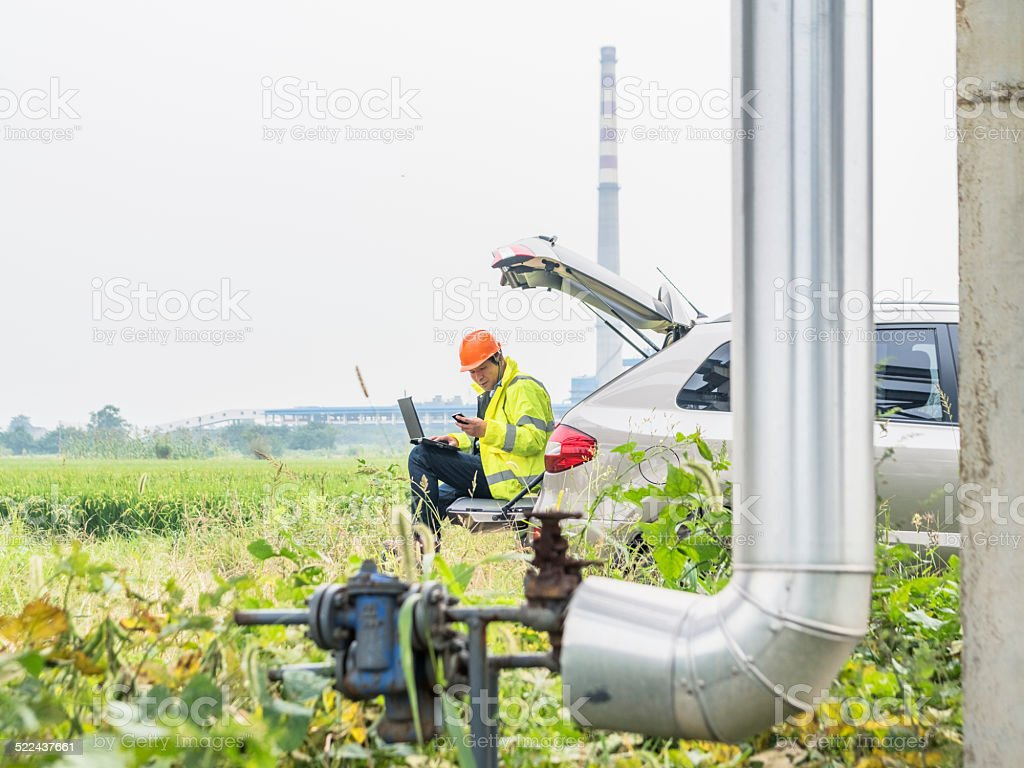 Natural gas plant engineers using laptop stock photo