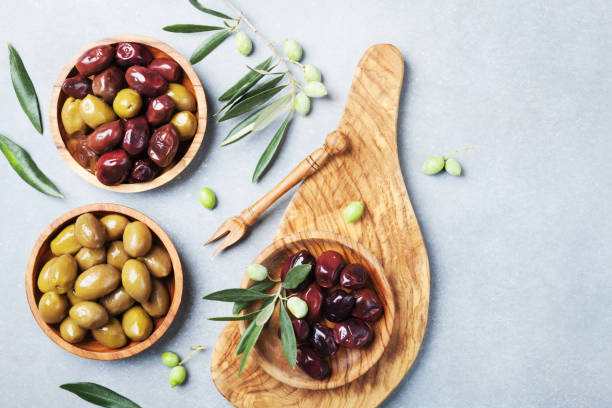 Natural greek olives in bowls with kitchen board from olive tree top view. Natural greek olives in bowls with kitchen board from natural olive tree top view. olives stock pictures, royalty-free photos & images