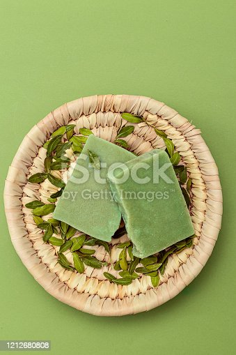 Natural green soap and eucalyptus leaves on a straw plate. Vertical format. Organic