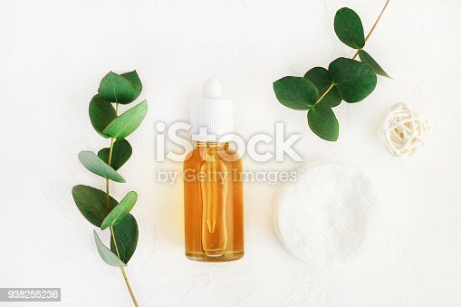 bottle with diy cleansing beauty care product and fresh green leaves viewed above on white, wellness background