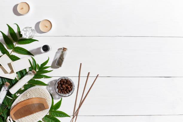 handgemachte naturseifen mit kaffeebohnen, meersalz, luffa, braun handtuch und grüne blätter auf weißem holz hintergrund - badewanne holz stock-fotos und bilder