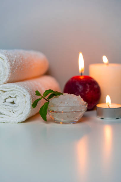 Natural health and SPA treatments vertical photo. White towels, sea salt in a cup, candles. stock photo