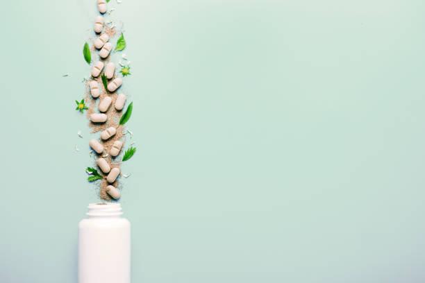 natürliche pflanzliche zusatzstoffe aus kräutern, aus dem weißen glas gegossen. das konzept einer gesunden ernährung. detox - nahrungsergänzungsmittel stock-fotos und bilder