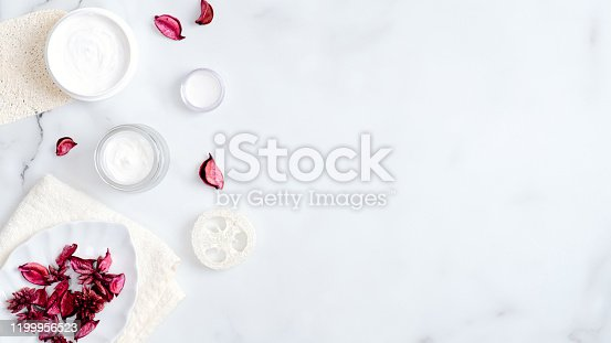 1128479585 istock photo Natural herbal spa cosmetic hygienic cream jars, luffa sponge, towel, pink flower petal on marble background. Flat lay, top view, copy space. Hand skin care, organic beauty products concept 1199956523