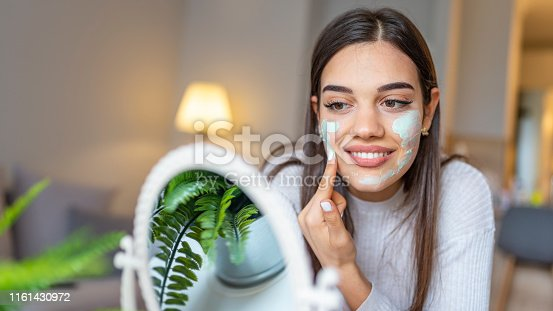 Natural homemade facial masks at home. Woman applying mask on her face and looking in the mirror. Beautiful woman applying natural facial mask. Beauty treatments.