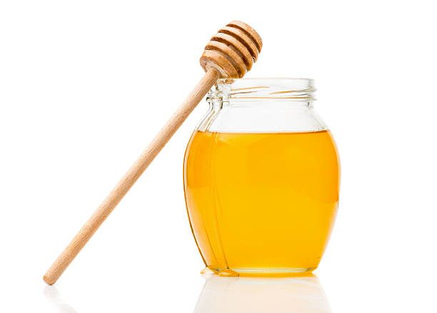Natural honey in a glass jar stock photo