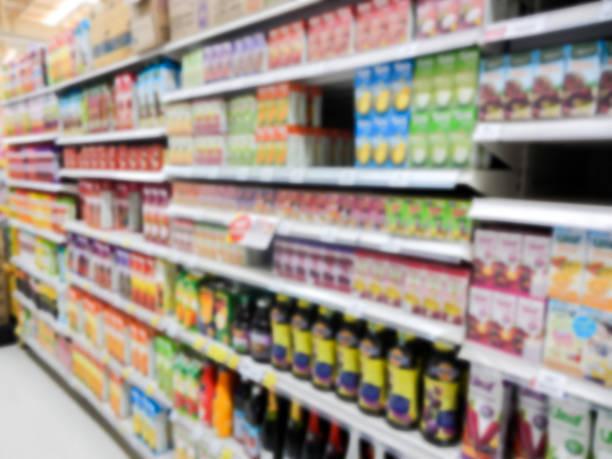 Des bouteilles de jus de fruits dans un supermarché flou d'arrière-plan - Photo