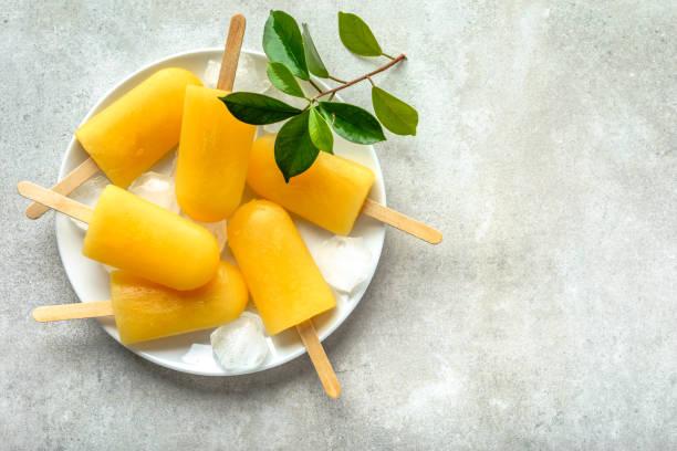 natürliche saftige orange eis am stiel. erfrischende eis am stiel, gemeinkosten, flach - mango eis am stiel stock-fotos und bilder