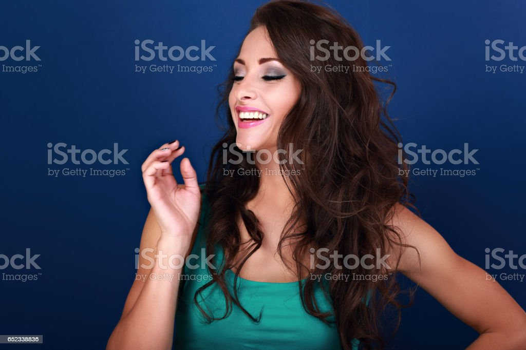 Natural laughing beautiful emotional curly long hair style woman looking with hand near the face on bright blue background stock photo