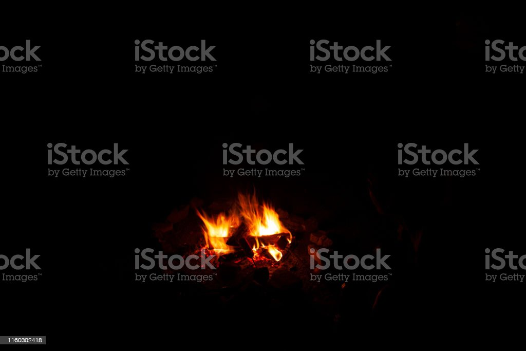 Campfire in the middle of the dark of the night while a sausage is...