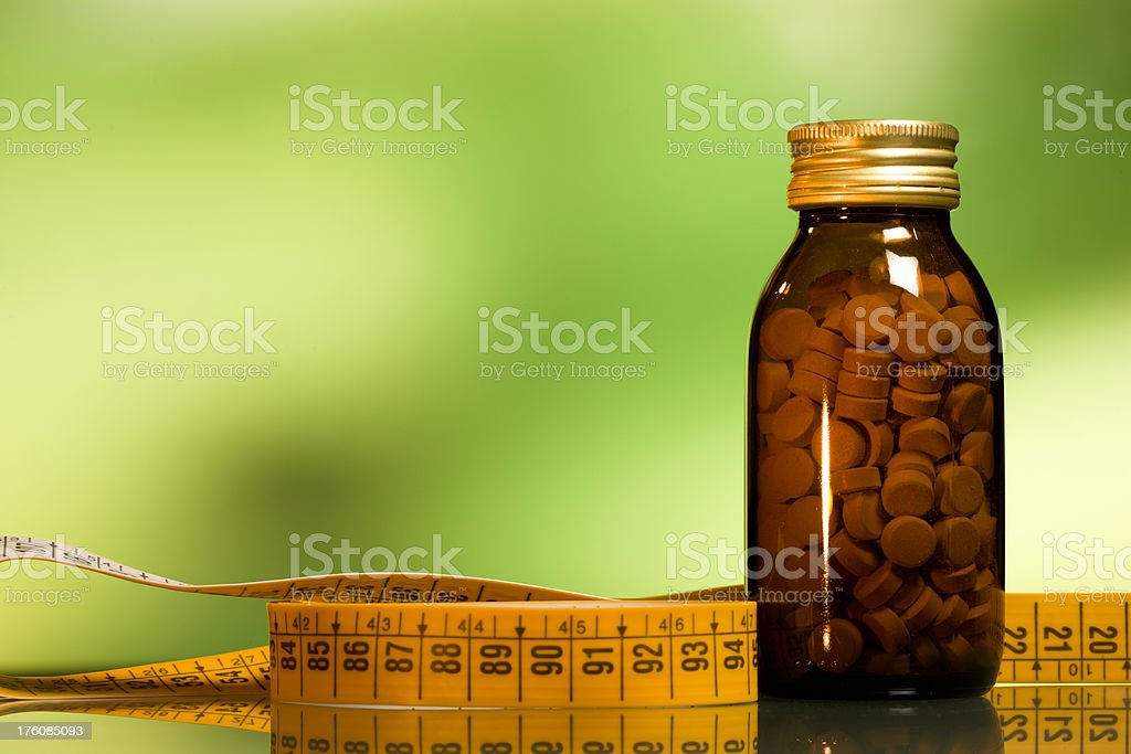 natural medicines, pills,glass bottle, tape measure royalty-free stock photo