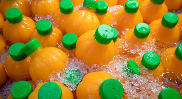 suco de laranja natural em garrafas de laranja forma em gelo picado. bebida refrescante com alta de vitamina c para o verão. - squeeze bottle - fotografias e filmes do acervo