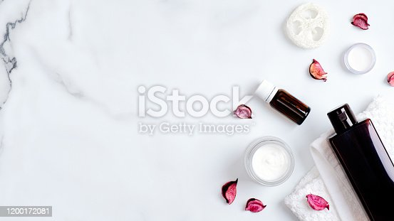 1128479585 istock photo SPA natural organic bath oil, lotion, cream with bath towel and rose flower petals on marble background. Body care, clean skincare, SPA concept. Flat lay, top view, copy space 1200172081