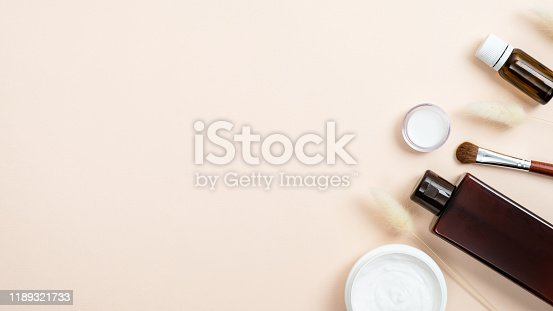 847096968 istock photo Natural organic beauty product concept. Cosmetics SPA bottle containers mockup, face cream and accessories on pastel beige background. Flat lay, top view. 1189321733