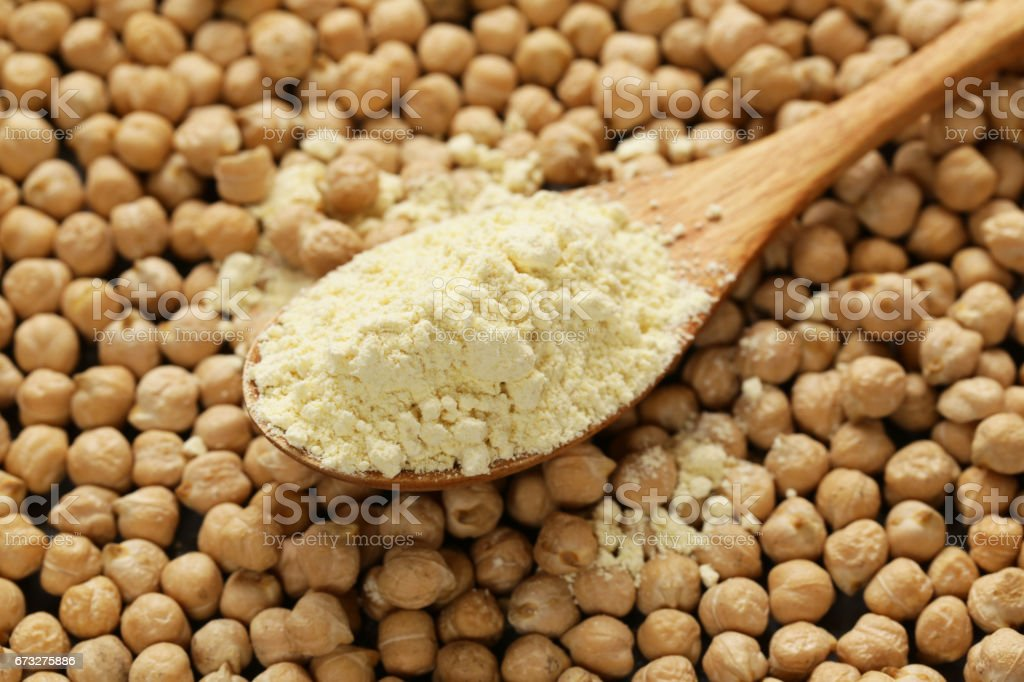 Natural organic chick pea flour in a wooden spoon stock photo