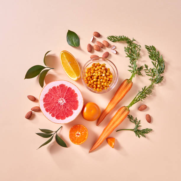 Natural organic citrus fruits, carrots, sea buckthorn berries - ingredients for making homemade detox smoothie on yellow paper background. stock photo