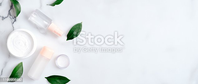1128479585 istock photo Natural organic cosmetic lotion bottles and hand cream on marble background with green leaves. Flat lay, top view, copy space. Beauty blog banner template. Hand skincare, body care concept 1199956482