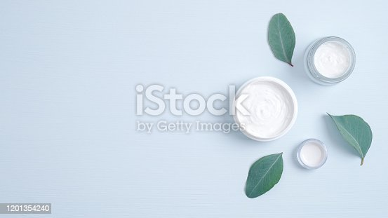 istock Natural organic cosmetic product concept. Hand care herbal cream in jars and green leaves. Banner mockup for beauty salon or eco shop. Minimalist flat lay style set. 1201354240
