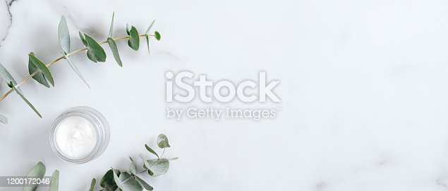 1128479585 istock photo Natural organic cream jar with eucalyptus leaves on marble background. Flat lay, top view, copy space. Natural organic product, beauty and spa concept 1200172046