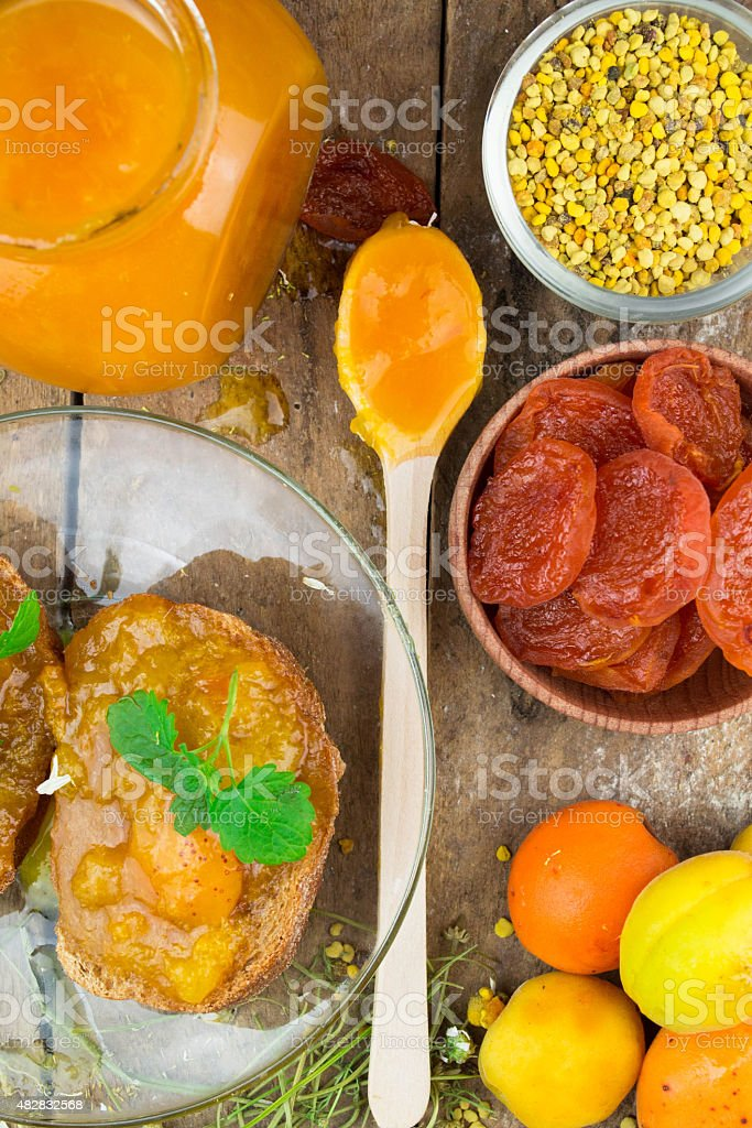 Natural organic dried apricots, apricot jam, and pollen stock photo