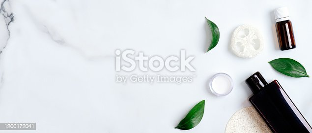 1128479585 istock photo Natural organic eco cosmetic products set with green leaves on marble background. Flat lay shampoo bottle, essential oil, face cream and bath accessories. Beauty and spa concept 1200172041