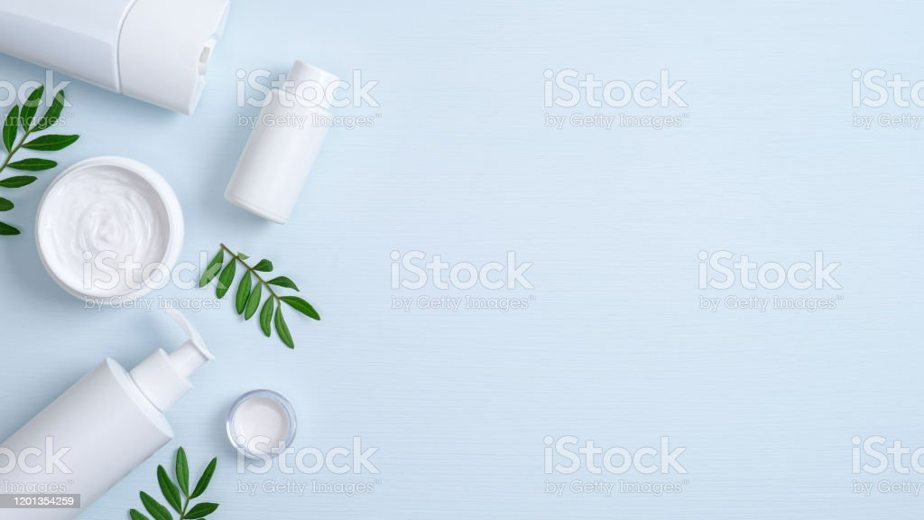 Natural Organic Spa Cosmetic Products Set With Green Leaves Top View Herbal Skincare Beauty Products On Blue Background Body Cream Essential Oil Liquid Soap And Shampoo Bottle Skin Care Concept Stock Photo