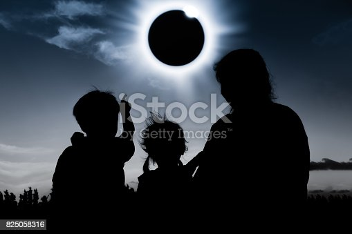 istock Natural phenomenon. Silhouette of family sitting and relaxing together. 825058316
