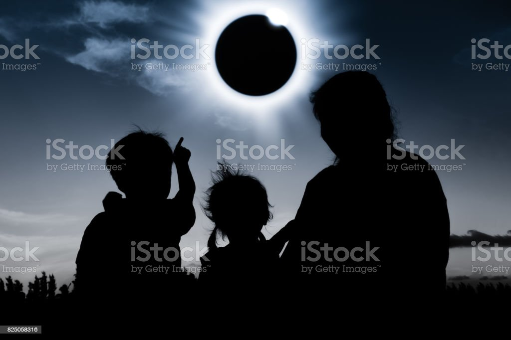 Natural phenomenon. Silhouette of family sitting and relaxing together. stock photo