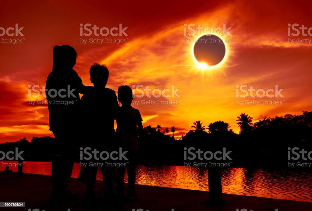 Natural phenomenon. Three looking at looking at total solar eclipse. stock photo