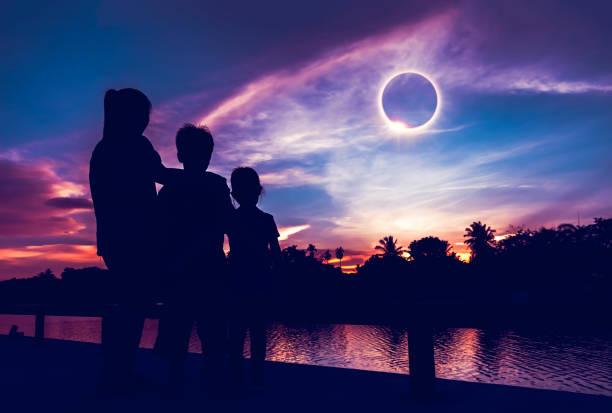 Natural phenomenon. Three person looking at total solar eclipse. stock photo