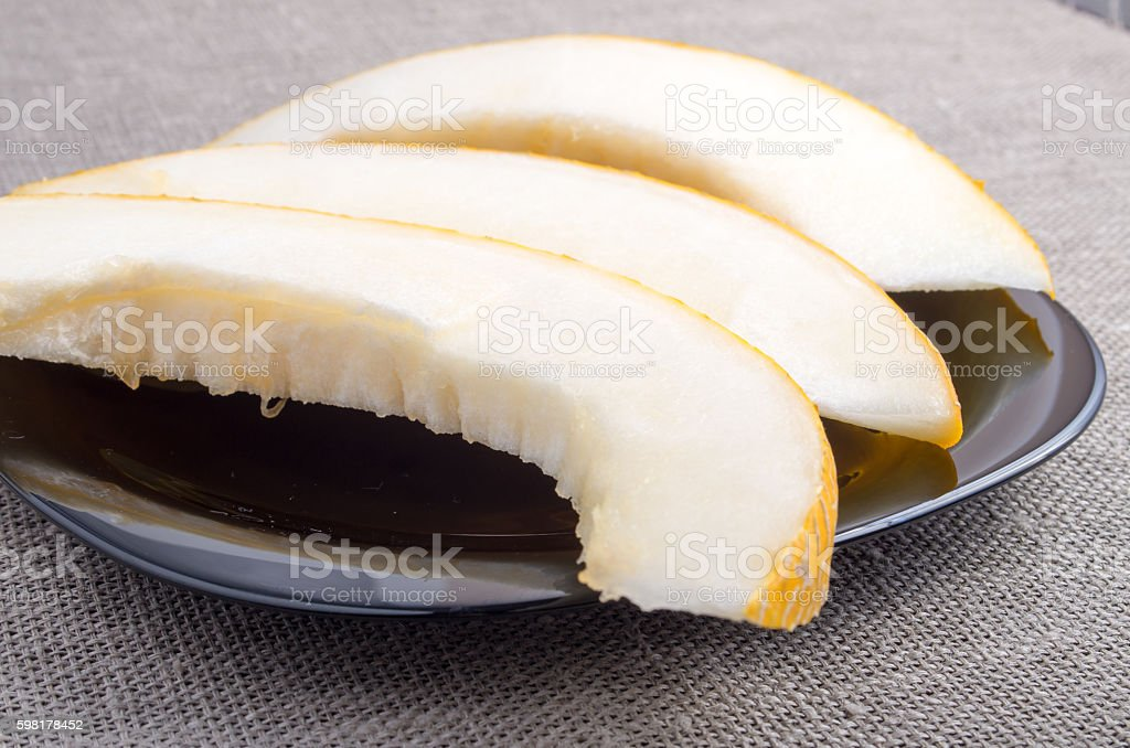 Natural pieces of yellow melon on a black plate foto royalty-free