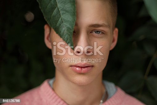 846124694 istock photo Natural portrait of a handsome man with freckles near green leaves 846126786