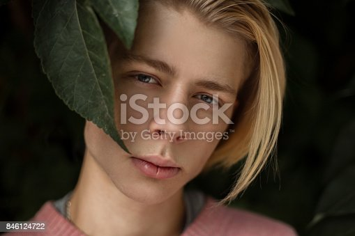846124694 istock photo Natural portrait of a handsome young man with a blonde hairstyle in the foliage 846124722