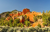 A natural wall of red sandstone stands high atop a sandy ridge at Red Rock Canyon in Utah.