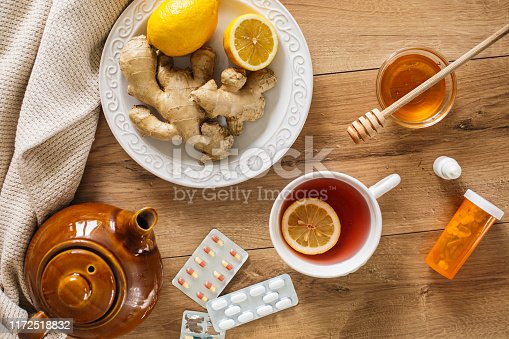 Flat lay of natural remedies against a cold and flu such as tea with lemon, honey, ginger and some prescription medication.