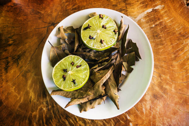 Natural repellent plate with lime, cloves and laurel on wooden table stock photo