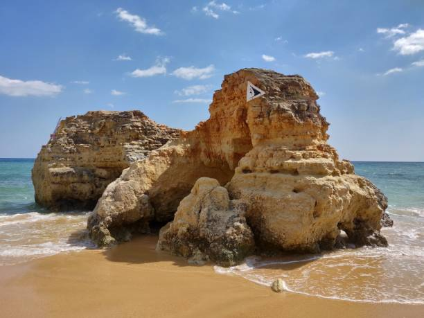 Natural rock in Albufeira water's edge. stock photo