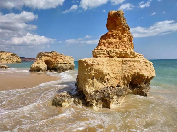 Natural rocks in Albufeira water's edge. stock photo