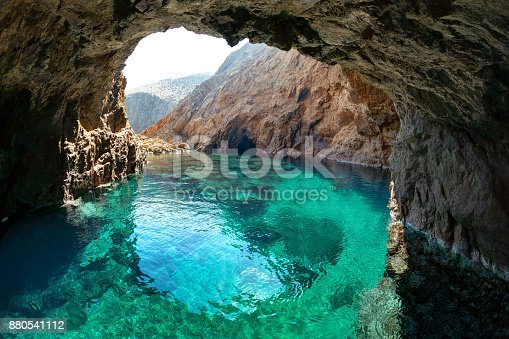 Natural rocky arch with clear transparent waters, in Tragonissi islet, Myconos, Greece