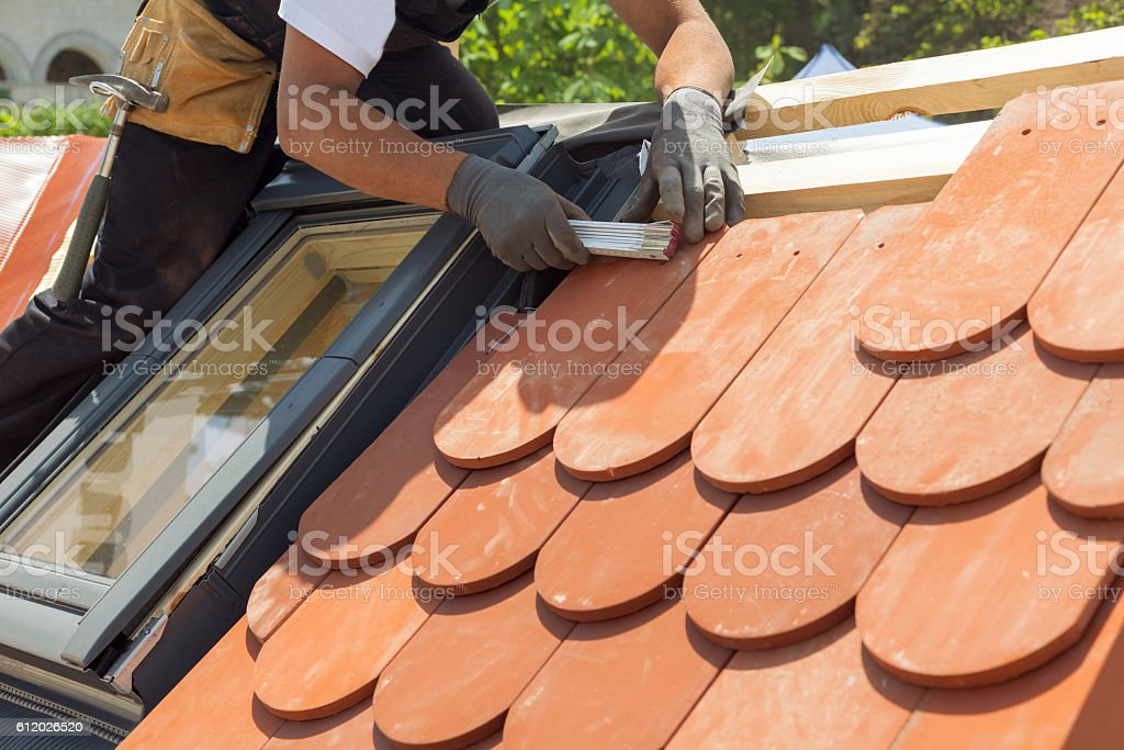 Natural roof tile instaalation. Roof with mansard windows. stock photo