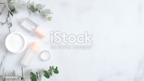1128479585 istock photo Natural skin care cosmetic cream and lotion with eucalyptus leaves on marble background. Organic spa beauty products. Skincare and body care concept. Flat lay, top view, copy space 1199956492