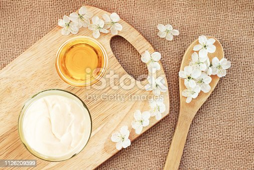 istock Natural skincare body butter cream, glass jar with honey, fresh blossom top view 1126209399