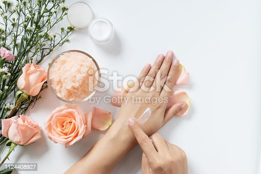 istock natural skincare concept. woman apply white cream on her hands on white background with jar of cosmetic cream, salt spa scrub ,rose and  white flowers with copy space 1124408927