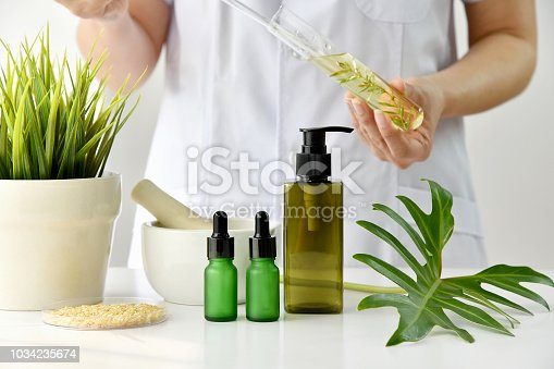 istock Natural skincare cosmetics research and development concept, Doctor formulating new beauty products from organic natural plants, Pharmacist mixing extract essence substance in test tube with container package. 1034235674