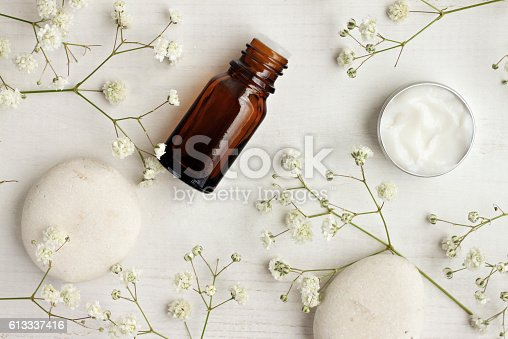 istock Natural skincare products,white stones and flowers, top view. 613337416