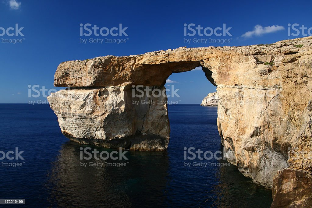 A natural stone archway in the ocean stock photo