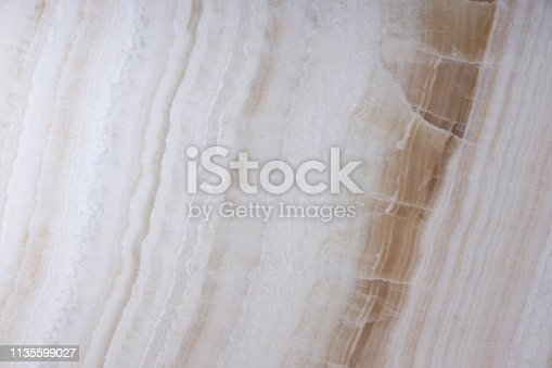 Natural stone of white color with brown veins, called Onyx.