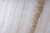Natural stone of white color with brown veins, called Onyx