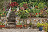 istock Natural stone steps and retaining wall, planter and garden border framing home entrance. Beautiful hardscape, colorful landscape design 1287214087